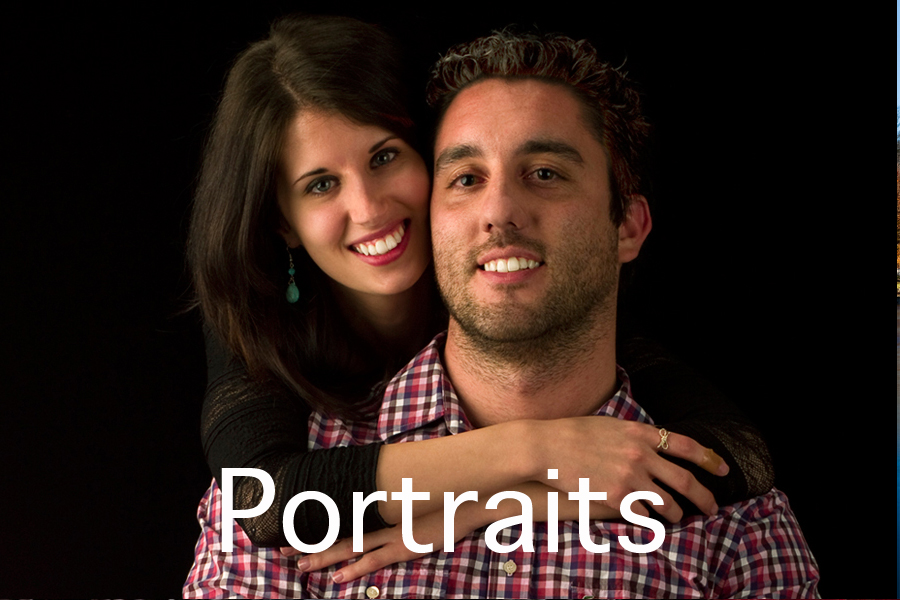 Portraits button. This is a Brian Charles Steel photograph of Kyle and Nikki.  Nikki is behind Kyle with her arms around him while hanging over his shoulders with her face beside his. They are both smiling, and looking into the camera.  She has long brown hair, and he has short curly hair.  They are towards the right side of the frame, and are seen from the chest up.  The background is solid black.