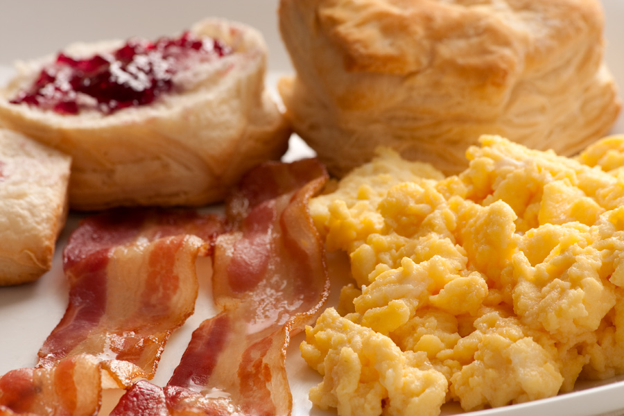 This Brian Charles Steel food photograph is a close up of breakfast food.  In the front right side is a pile of scrambled eggs. Behind the eggs is a biscuit with jelly on it.  To the left of the eggs are two diagonal strips of bacon.  The light is soft.  The depth of field is shallow.  The eggs and bacon are in focus but the biscuits are soft.