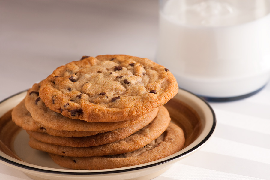 This Brian Charles Steel food photograph is of a stack of chocolate chip cookies and a glass of milk.  The cookies are in the front left portion of the frame on a light brown ceramic plate.  They are stacked at a slight angle extending out towards the glass of milk.  The glass of milk is in the back right portion of the frame.  Milk comes across as blue on camera, so the milk glass is actually filled with Elmer's glue.