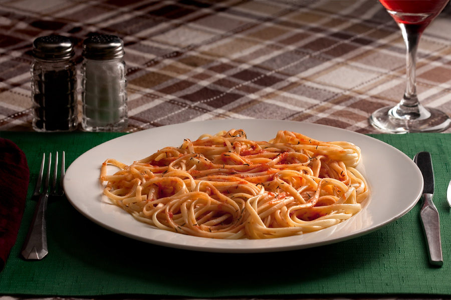 This is a Brian Charles Steel photograph of a plate of spaghetti on a brownish plaid tablecloth.  The white plate of spaghetti is sitting on a green placemat that is on the tablecloth.  The pasta has red sauce on it, and the noodles are neatly coiled, so that there are no visible loose ends.  The image was shot at a downward angle from above.  To the left and behind the plate are salt and pepper shakers.  On the sides of the plate are a fork, spoon and knife.  Behind the plate on the right side is a glass of red wine.  The pasta is lit from the back right side.