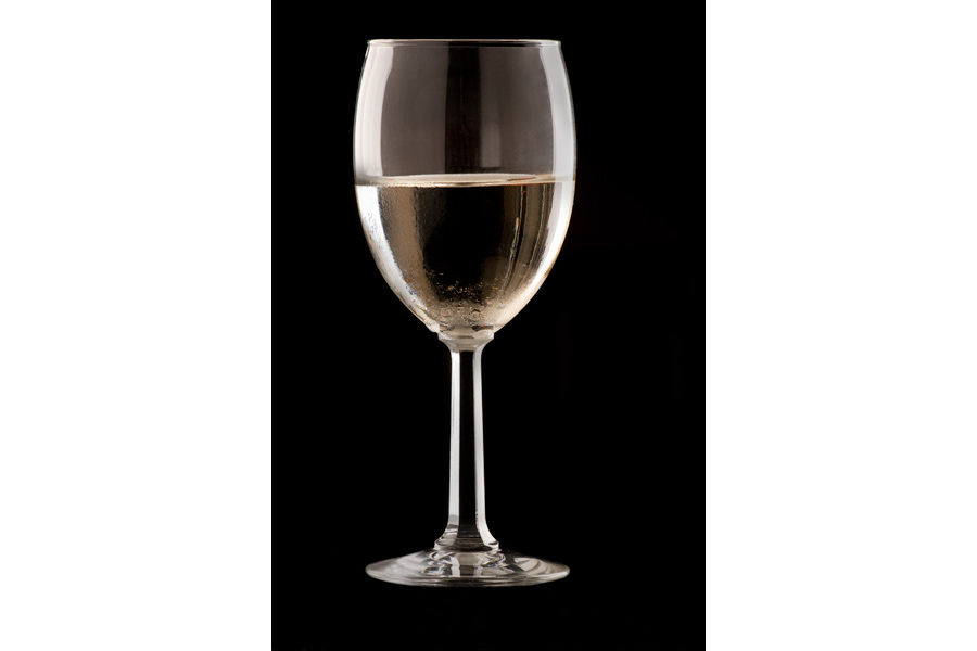 This is a Brian Charles Steel photograph of a glass of white wine in a wine glass.  The image is a vertical shot, and the glass takes up most of the frame.  The glass is on a black background.  There are highlights on the far right and left sides of the glass.  There are beads of condensation on the glass.