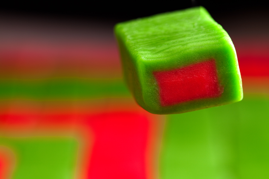 This is a Brian Charles Steel photograph of a piece of red and green Hubba Bubba gum floating above red and green gum.  The piece is rectangular; it is red in the center and green on the outside.