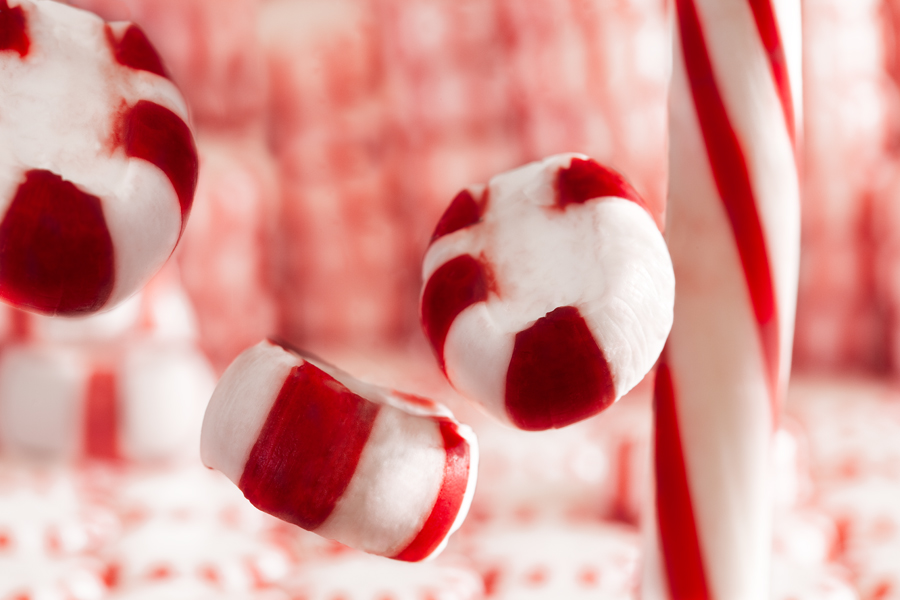 This Brian Charles Steel photograph is composed of a peppermint stick, oval shaped peppermints and circular peppermints. The circular peppermints compose the background in stacks and are out of focus. On the right side there is peppermint stick going straight down from top to bottom. In front of the stick was an oval shaped peppermint floating near the top center. Below the floating mint was another floating oval shaped mint. There was another floating mint in the top left corner.
