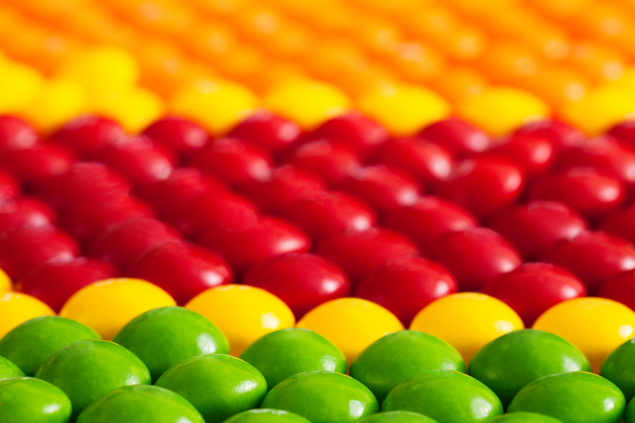 This Brian Charles Steel Photograph is composed of round candy in various colors. The candies are arranged in horizontal rows of the same color. The bottom portion of the frame has two rows of green candy. A single row of yellow candy borders the green candy. Behind the yellow candy are rows of red candy, and there is a row of yellow candy on the side. The top portion is filled with orange candy.