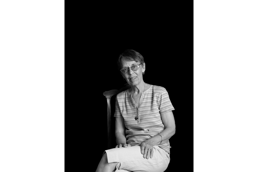 This is a Brian Charles Steel black and white photographic portrait of Sandy Brauer sitting in a chair.  She is in the lower middle portion of the frame.  She is shown from just below the knees and up.  She is wearing a short sleeve shirt with horizontal stripes and plain white shorts that go to the knees.  She has her legs crossed facing toward the left.  Her upper body is facing forward and she is looking into the camera.  Her hands are on her legs.  She has short brown hair and is wearing glasses.  The background is solid black.