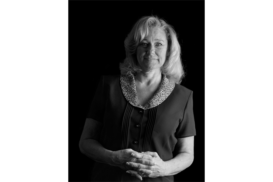 This is a Brian Charles Steel black and white photographic portrait of Allison Kerr.  She is positioned toward the center, and lit with a Rembrandt style.  The main light source is coming from the right.  She is shown from the waist up, and she looks directly into the camera.  Kerr has shoulder length blond straight blond hair.  She is holding her hands together over her stomach.  Kerr is wearing a short-sleeved button up shirt. The background is solid black.