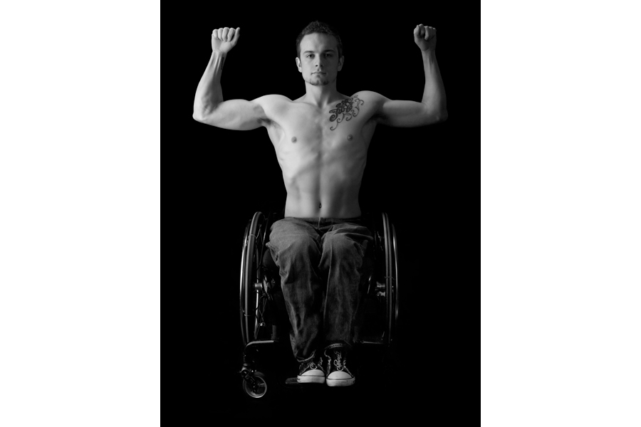 This is a Brian Charles Steel black and white photographic portrait of Richard Corbett.  He is positioned in the center of the frame.  He is flexing his arms up in the air in a bodybuilding pose.  He is seated in a wheel chair while wearing blue jeans and no shirt.  He is lit in a Rembrandt style with the main light coming from the left.  The light is soft.