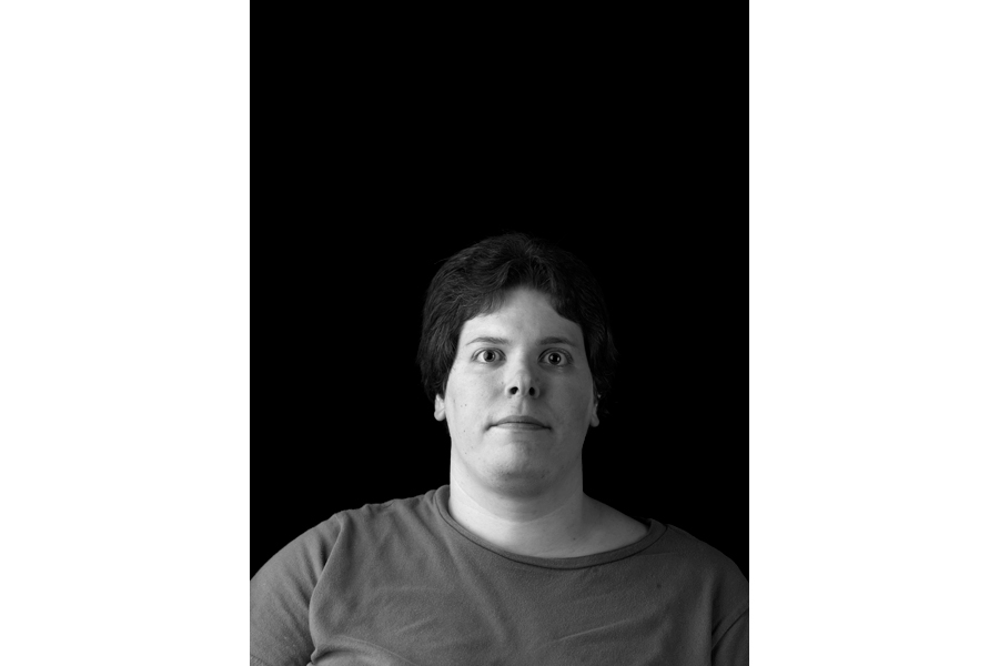 This is a Brian Charles Steel black and white photographic portrait of Tiffany Coleman.  She occupies the bottom half of the frame, and is shown from the chest up.  She has short dark hair, and is wearing a grey shirt.  Coleman is facing forward, and looking straight into the camera.  She occupies about one third of the frame. Coleman is lit with Rembrandt lighting with the main source coming from the left.  The background is solid black.