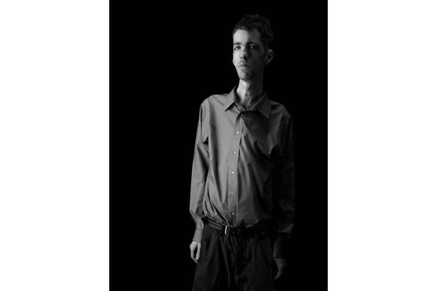 This is a black and white photographic portrait of photographer Brian Charles Steel.  Steel has congenital fiber type disproportion, which causes him to be thin and small framed.  Steel is positioned on the right side of the frame and he fills it from top to bottom on that side.  You see him from just above the knees and up.  He is wearing a long sleeved dress shirt with dress slacks.  His arms are at his side and he is looking straight into the camera.  He is lit in a Rembrandt style with the main light source coming from the left.