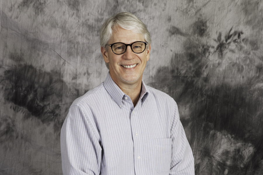 This Brian Charles Steel Photograph is a portrait of a man with grey hair in a blue and white striped shirt. He is seated in front of a grey background.  He is also wearing glasses.