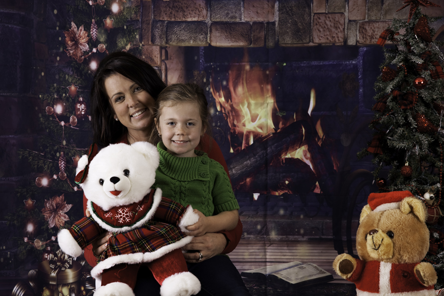 This Brian Charles Steel photograph is a Christmas portrait of a woman and her daughter.  Behind them is a brick fireplace with a roaring fire. On the left side of the background is a Christmas tree, and on the right is a teddy bear dressed like Santa.  The woman has long black hair, and the little girl has light brown hair.  The girl is holding a white teddy bear wearing a red and green plaid dress.