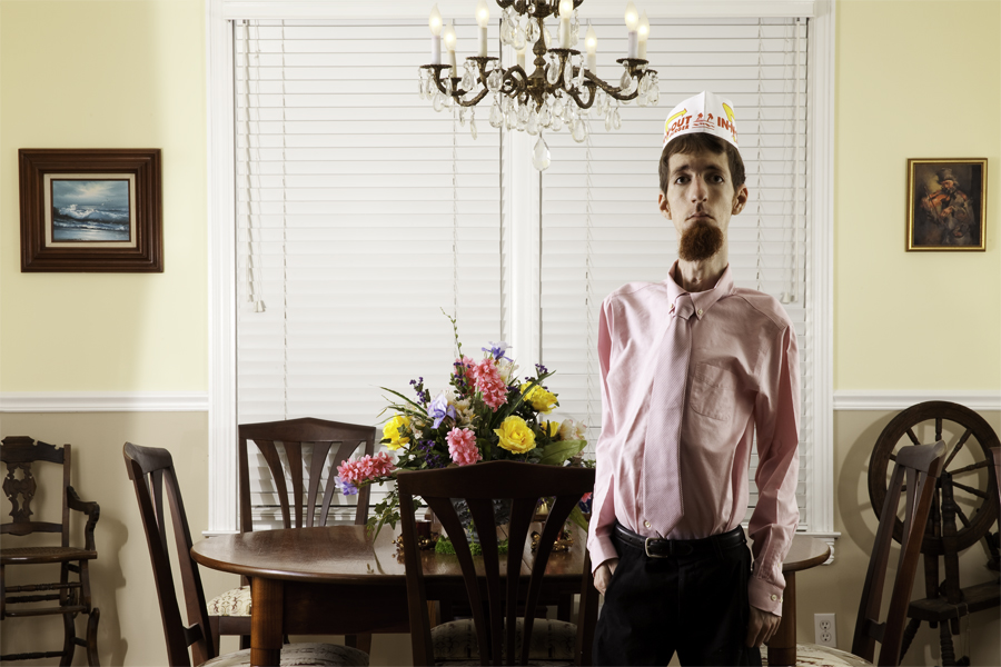 This Brian Charles Steel photo is a self-portrait of the artist in a dining room. He is standing in front of the wooden dining room table with his hands in his pockets.  The table has a vase of flowers on top of it. Above the table is a chandelier.  He is lit dramatically; both side so him are well lit, but his front is in shadow.  He is wearing black dress pants, pink dress shirt, a pink tie, and an In And Out cap.  His hair is short and brown. On the wall behind him on the right there is an ocean painting and a wooden high chair.