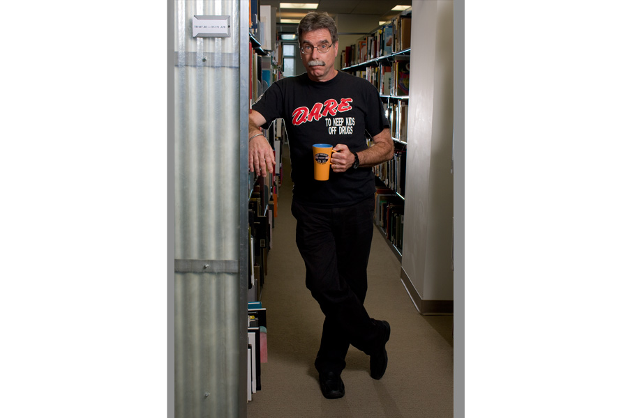 This is a Brian Charles Steel portrait of photographer Forest McMullin.  He is in a library between to book aisles.  He is wearing a black Dare shirt, and holding a coffee cup. His body is completely in frame, and he comprises about half of the frame.  He is positioned in the center.