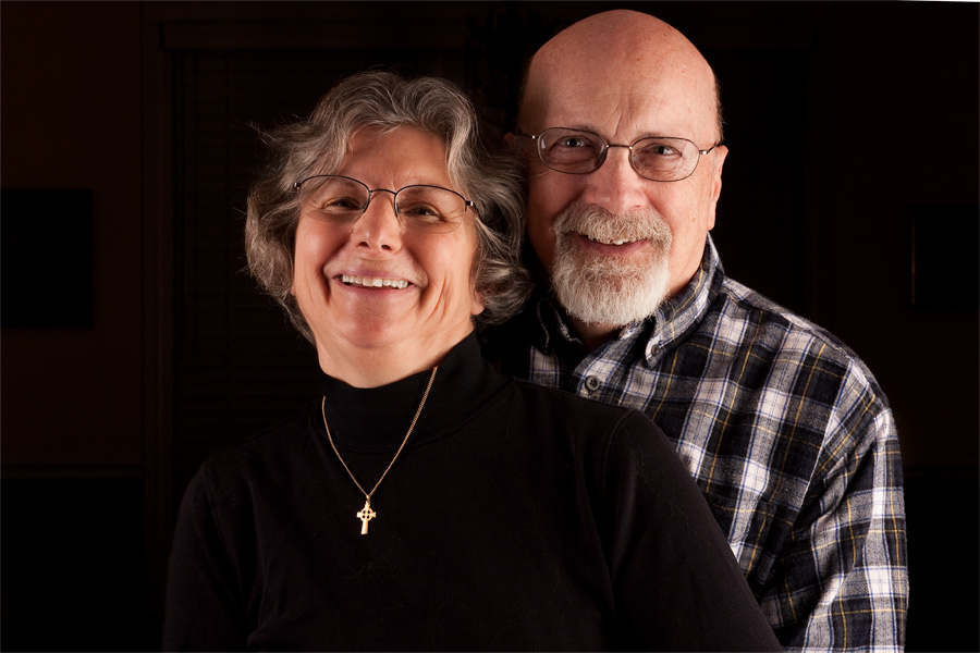 This is a Brian Charles Steel photographic portrait of John and Hazel.  They are toward the center of the frame.  John is wearing a plaid shirt and Hazel is dressed in black with a gold necklace. They are smiling.  They are shown from the chest up and comprise about three fourths of the frame.  They are lit from the front right side.