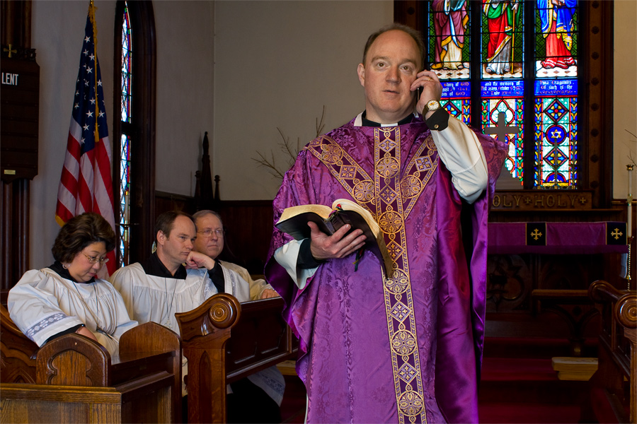 This is a Brian Charles Steel portrait of an Episcopal priest talking on his cell phone during a service.  He is in the center of the frame.  There is stained glass behind him to the right. To the left of him are choir members who appear to be frustrated him for being on the phone.  He holds is bible in his right hand and a phone in his left.