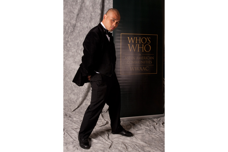 This Brian Charles Steel photo depicts a young Asian gentleman in front a grey back drop. He is wearing a tuxedo, and has his side turned to the camera.  Behind him is a banner for the Who's Who in Asian American Communities.