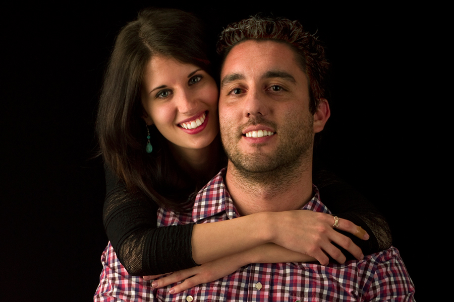 This is a Brian Charles Steel photograph of Kyle and Nikki.  Nikki is behind Kyle with her arms around him while hanging over his shoulders with her face beside his. They are both smiling, and looking into the camera.  She has long brown hair, and he has short curly hair.  They are towards the right side of the frame, and are seen from the chest up.  The background is solid black.
